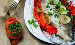Baked fish with bell peppers, onions and herbs Stock Photography