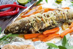 Baked fish with carrots and onions in foil Stock Photography