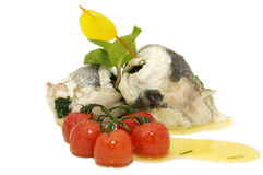 Baked fish with cherry. Tomatoes on a white background royalty free stock photos