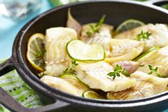 Baked fish fillet with lime and garlic Stock Photos
