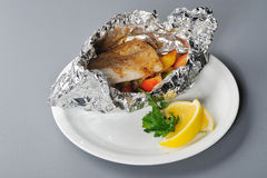 Baked fish in foil royalty free stock photo