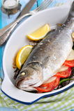 Baked fish with herbs, vegetables and garlic, selective focus Stock Image