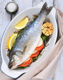 Baked fish with herbs, vegetables and garlic, selective focus Stock Photos