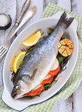 Baked fish with herbs, vegetables and garlic, selective focus Stock Images