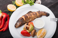 Baked fish with lemon and grilled vegetables Stock Photo