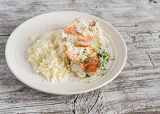 Baked fish with lemon and herbs and cous cous on a white plate, on bright wooden surface. Healthy food Stock Photos