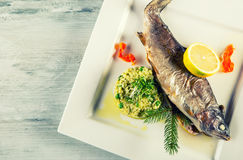 Baked fish on a plate with lemon and barley groats in a restaurant Stock Image
