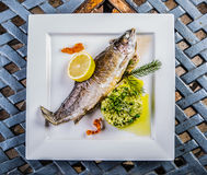 Baked fish on a plate with lemon and barley groats in a restaurant Royalty Free Stock Images