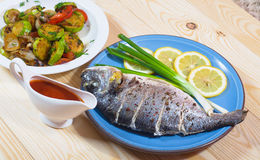 Baked fish on plate with lemons, and green onion. Baked fish on plate with lemons,  grilled vegetables and green onion Stock Photo
