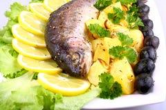 Baked fish with potatoes, black olives, lemon and salad Royalty Free Stock Photos
