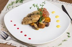 Baked fish with potatoes and mushrooms on white plate Stock Photography