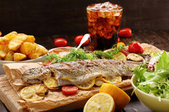 Baked fish with roasted potatoes and salad Royalty Free Stock Photo