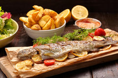 Baked fish with roasted potatoes and salad Stock Photos