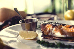 Baked fish with rosemary, sauce and lemon on a Stock Images