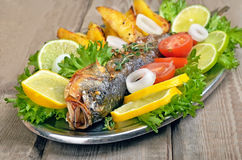 Baked fish on rustic table Royalty Free Stock Image
