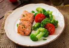 Baked fish salmon garnished with broccoli and tomato. Dietary menu. Fish menu. Seafood - salmon royalty free stock photos