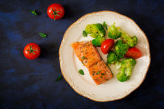 Baked fish salmon garnished with broccoli and tomato. Dietary menu. Royalty Free Stock Images