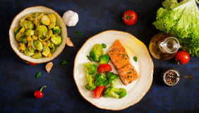Baked fish salmon garnished with broccoli and tomato. Dietary menu. Stock Photography