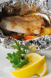 Baked fish in sauce. Baked in foil cod with lemon and sauce stock image
