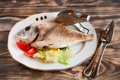 Baked fish stuffed with vegetables on a white plate on a wooden Stock Images