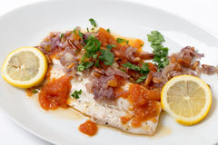 Baked fish with tomato sauce, onion, pine nuts Royalty Free Stock Photos