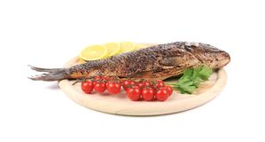 Baked fish on wooden board Stock Image