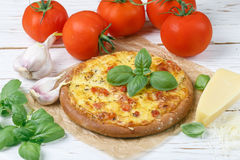 Baked flat bread with tomatoes, cheese, garlic and Basil. On a white wooden table. Rustic style. Top view Stock Photos
