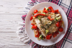 Baked flounder with seasonal vegetables. horizontal top view. Delicious baked flounder with seasonal vegetables on a plate. horizontal view from above Royalty Free Stock Images