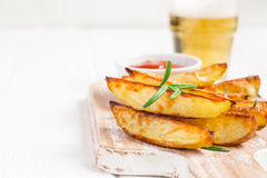 Baked fried potatoes with rosemary and tomato sauce on a white background, selective focus Stock Photography