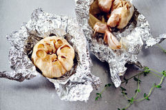 Baked garlic. In foil with thyme branches Stock Photography