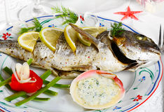 Baked gilt-head bream. Gilt-head bream baked with lemon and served by vegetables  and sauce in seashell Stock Photo
