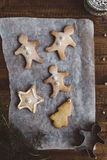 Baked Gingerbread Men, Star and Christmas Tree Biscuits on Parchment Paper on Rustic Wooden Table with Silver Sugar Balls Stock Images