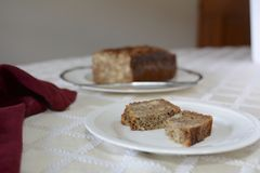 Baked gluten free banana bread on a white plate sitting on a table stock photography