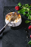 Baked Goat cheese with honey and raspberries. Grilled goat cheese served on black slate board with liquid honey, lavender, raspberries, and green salad. With Stock Photo