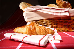 Baked goods. Croissant on white - red tablecloth close up Stock Photos