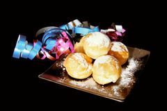 Baked goods and garlands. Some baked goods with wipped cream on a plate with garlands royalty free stock images