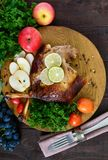 Baked goose legs, served with apples, vegetables, grapes, greens on a round oak tray. On a dark wooden table. Top view Royalty Free Stock Image