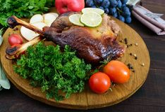 Baked goose legs, served with apples, vegetables, grapes, greens on a round oak tray. On a dark wooden table royalty free stock photos