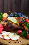 Baked goose legs, served with apples, vegetables, grapes, greens on a round oak tray. On a dark wooden table. Vertical view Stock Images