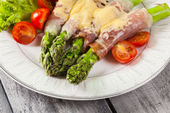 Baked green asparagus with prosciutto and cheese Royalty Free Stock Photo
