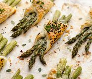 Baked green asparagus in puff pastry sprinkled with sesame seeds, nigella seeds and fresh thyme on a white background, close-up, t stock photography