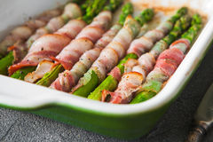 Baked green asparagus wrapped with bacon Stock Images