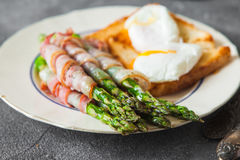 Baked green asparagus wrapped with bacon Stock Photo