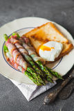 Baked green asparagus wrapped with bacon Stock Image