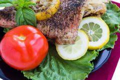 Baked grouper served with lemon and basil on black plate Stock Image