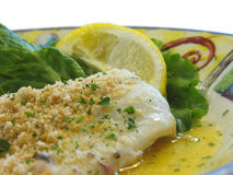 Baked haddock. With cracker crumbs and a lemon for garnish Royalty Free Stock Photography