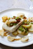 Halibut with baby potatoes, broad beans and chorizo. Baked halibut with baby potatoes, broad beans and chorizo Royalty Free Stock Images