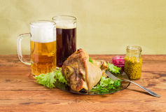 Baked ham hock, condiments, lager beer and dark beer Royalty Free Stock Image