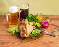 Baked ham hock, condiments, lager beer and dark beer Stock Photos