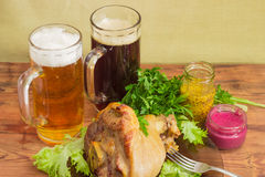 Baked ham hock, condiments, lager beer and dark beer Stock Photo